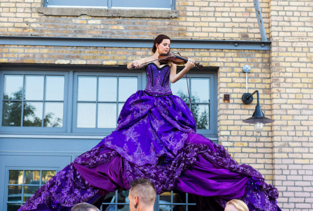Purple violinist archway installation Enticing Entertainment provided for their event showcase. This event was held an the Machine Shop venue in Minneapolis. These characters greeted guests as they entered underneath the dress of the violinist.